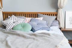 时髦的与黑色的卧室室内设计仿造了在床和装饰台灯上的枕头 免版税库存照片