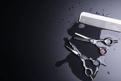 时髦的专业理发师剪刀和白色梳子在黑bac 免版税库存图片