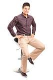 时髦的人坐一把现代椅子 免版税库存照片