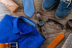 时髦的人衣物和辅助部件平的位置在蓝色和棕色颜色在木背景 库存图片