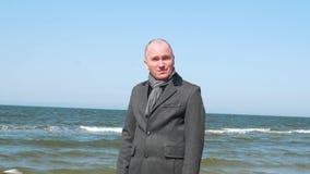 时髦的人陈列告诉我姿态标志 在海滩的典雅和确信的年轻商人 事务和旅行 股票录像
