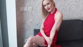时髦的典雅的白肤金发的妇女在家庭客厅,佩带的红色性感的礼服 股票录像