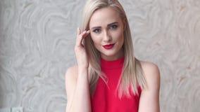 时髦的典雅的白肤金发的妇女在家庭客厅,佩带的红色性感的礼服 股票视频