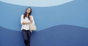 时髦的凉快的女孩对蓝色墙壁 库存照片