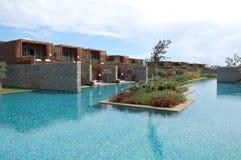 时髦的别墅、蓝色水池和花床的看法在豪华 免版税图库摄影