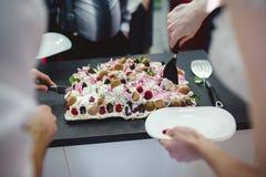 时髦的华美的新娘和典雅的新郎切口和品尝异常的白色婚宴喜饼 Pov视图 免版税库存照片