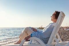 时髦的可爱的成熟妇女坐在12月的50-60岁 免版税库存照片