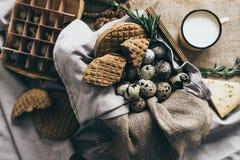 时髦的土气静物画用乳酪和不同的种类在米黄温暖的颜色的面包与作为a使用的工艺餐巾 库存图片