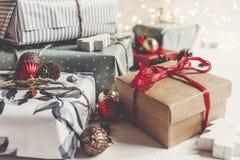 时髦的圣诞节包裹了与装饰品和光的礼物  免版税库存图片