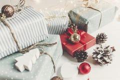 时髦的圣诞节包裹了与装饰品的在w的礼物和锥体 免版税图库摄影