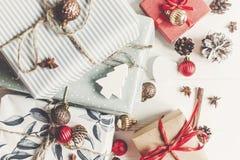 时髦的圣诞节包裹了与装饰品的在w的礼物和锥体 免版税库存图片