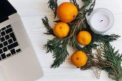 时髦的圣诞节舱内甲板位置 膝上型计算机和桔子和金黄星a 图库摄影
