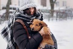 时髦的在多雪的co的行家妇女拥抱的和微笑的逗人喜爱的小狗 库存图片