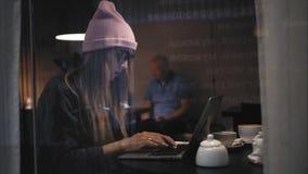 时髦的坐在咖啡馆和输入膝上型计算机的玻璃和帽子的行家妇女 视图通过视窗 股票视频