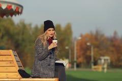 时髦的外套的时髦妇女坐长凳在城市公园 户外都市场面 饮用的外带的咖啡和文字或者凹道 免版税图库摄影