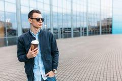时髦的太阳镜的人,一个人在城市附近走,并且从一纸杯的饮用的咖啡,一个英俊的人走动和r 免版税库存照片