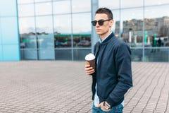 时髦的太阳镜的人,一个人在城市附近走,并且从一纸杯的饮用的咖啡,一个英俊的人走动和r 库存图片