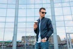 时髦的太阳镜的人,一个人在城市附近走,并且从一纸杯的饮用的咖啡,一个英俊的人走动和r 免版税库存图片