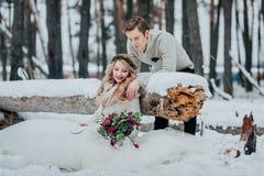 时髦的夫妇在多雪的森林冬天婚礼摆在 附庸风雅 库存图片