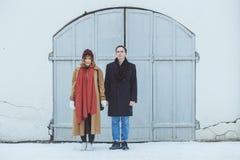 时髦的夫妇在站立在白色历史大厦附近的经典随员 时兴的冬天衣物 库存图片
