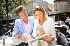 时髦的夫妇在选择菜单的室外餐馆 库存照片