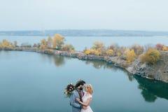时髦的夫妇新婚佳偶微笑和拥抱站立在湖前 新娘和新郎与dreadlocks看彼此 免版税库存图片