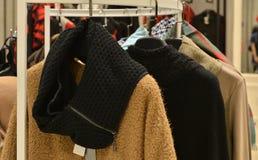 时髦的女人在挂衣架穿戴在衣物商店 图库摄影