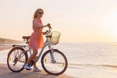 时髦的女人在海滩的骑马自行车在日落 免版税库存照片