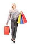 时髦的女人运载的购物袋 免版税库存图片