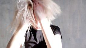时髦的女人金发碧眼的女人摆在与在灰色背景的头发 股票视频