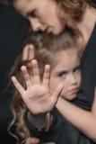 时髦的女儿和母亲拥抱在黑色的,做中止姿态的女孩 库存照片