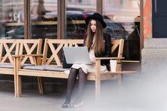 年轻时髦的女学生键盘输入的画象在她的网书的在开始前在大学演讲 库存图片