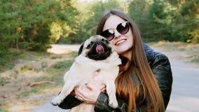 时髦的女孩拥抱爱抚滑稽的哈巴狗狗画象在慢动作的公园 股票视频