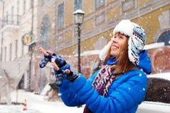 年轻时髦的女孩高兴第一雪 雪在城市 让雪 女孩抓住雪用他的手 免版税库存图片