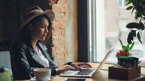 时髦的女实业家与在咖啡馆键入的坐的膝上型计算机一起使用在单独桌上 影视素材