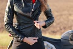 时髦的女性摩托车骑士的播种的图象用拉锁拉上黑皮夹克,有身体保护,为在摩托车的乘驾,喜欢做准备 免版税库存图片