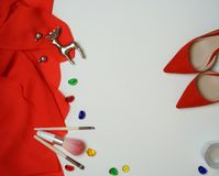 时髦的女性给辅助部件时尚成套装备穿衣:红色布料,鞋子构成掠过耳环鹿白色背景 新的圣诞节 免版税库存照片