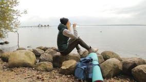 时髦的妇女侧视图有背包饮用水的从在海湾背景的瓶  股票视频