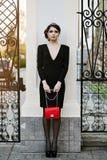 年轻时髦的妇女生活方式画象在有一个红色时髦袋子的城市进来 在女孩肩膀女用无带提包 库存图片