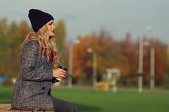 年轻时髦的妇女用咖啡在公园 免版税图库摄影