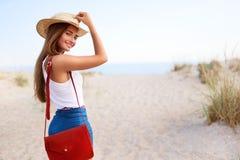 时髦的妇女走到在草帽、夏天牛仔布短裤和红色时兴的袋子的海滩 可爱的被晒黑的女性 免版税库存照片