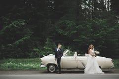 时髦的婚礼夫妇,新娘,亲吻和拥抱在减速火箭的汽车的新郎 库存图片