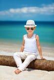时髦的孩子男孩坐棕榈树在海滩 免版税库存图片