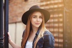 戴时髦的宽充满的黑帽会议的美丽的时兴的女孩画象看照相机 背景秀丽城市生活方式都市妇女年轻人 关闭 免版税库存照片