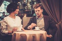 时髦的富裕的夫妇饮用的咖啡 免版税图库摄影