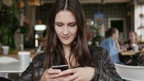 时髦的少妇使用一个智能手机送坐在现代咖啡馆的一张桌上的sms,微笑 4K 库存照片