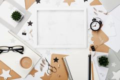 时髦的工作场所背景 框架、咖啡、办公用品、闹钟和笔记本在白色桌面看法 平的位置 复制空间 免版税库存照片