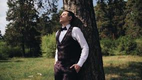 时髦的帅哥站立本质上倾斜反对树和闭上他的眼睛的 太阳在他的面孔发光 股票录像