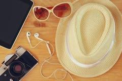 时髦的帽子妇女太阳镜老照相机和片剂设备顶视图在木桌 vaction和旅行概念 免版税图库摄影