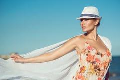 时髦的帽子的美丽的白肤金发的妇女和与花的明亮的上面打印看在旁边和对白色pareo负飞行由风 库存图片